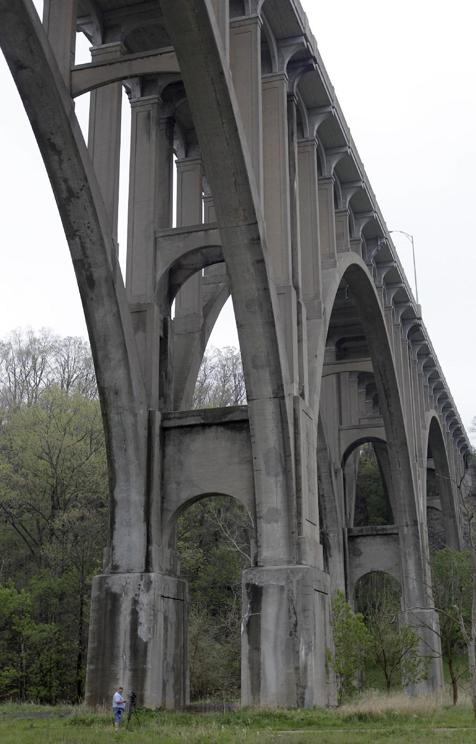 A cameraman stands beneath a bridge at the Cuyahoga Valley National Park in Brecksville, Ohio, on Tuesday, May 1, 2012. Five men have been arrested for conspiring to blow up the high level bridge over the Cuyahoga River valley, but there was no danger to the public because the explosives were inoperable and were controlled by an undercover FBI employee, the agency said Tuesday in announcing the men's arrests. (AP Photo/Amy Sancetta)