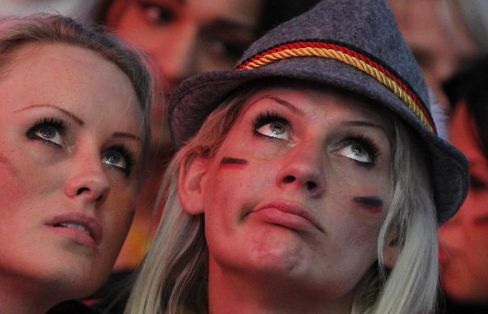 Two Germany supporter react as they watch the Euro 2012 soccer championship semifinal match between Germany and Italy at a public viewing event in Hamburg, northern Germany, Thursday, June 28, 2012. Germany lost 1-2 to Italy. (AP Photo/dapd, Philipp Guelland)