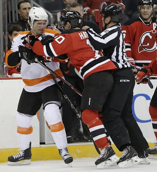 Philadelphia Flyers center Chris Vande Velde, left, scuffles with New Jersey Devils defenseman Peter Harrold, center, as linesman Steve Barton (59) tries to break them up during the first period of an NHL hockey game, Thursday, Sept. 26, 2013, in Newark, N.J. (AP Photo/Julio Cortez)