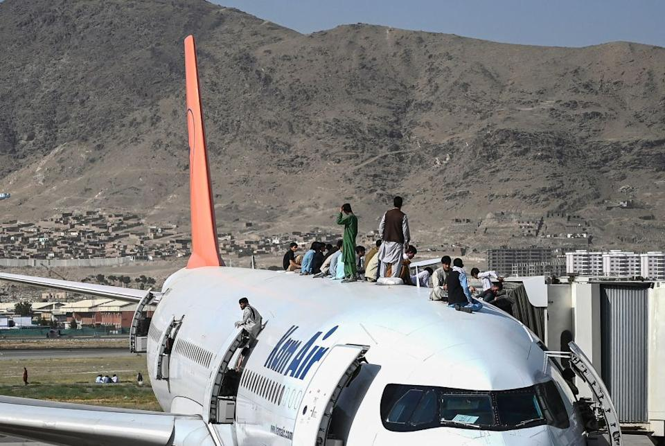 Afghan people climb atop a plane as they wait at the Kabul airport in Kabul.