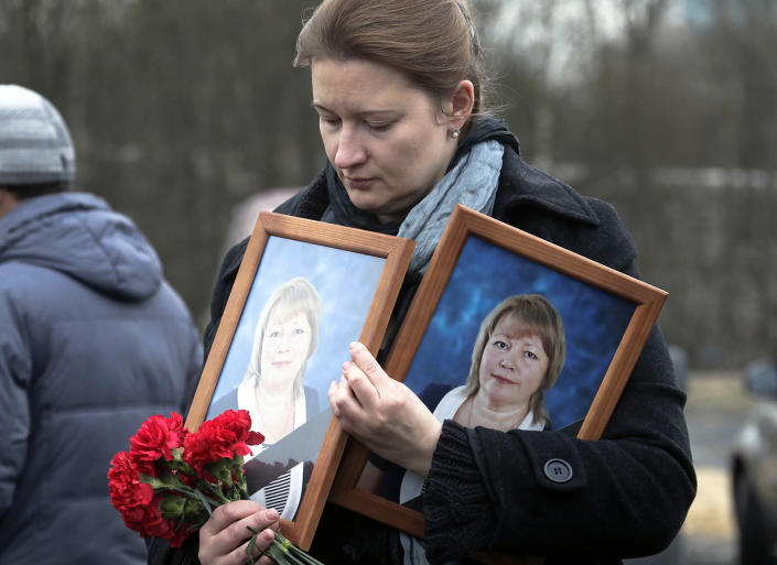 <p>A woman holds portraits of Irina Medyantseva, one of the victims of the subway explosion, during her funeral outside St. Petersburg, Russia, April 6, 2017. Medyantseva, a doll maker, died after she threw herself on her daughter to save her from the blast in the subway in Russia's St. Petersburg on Monday. (Photo: Dmitri Lovetsky/AP) </p>