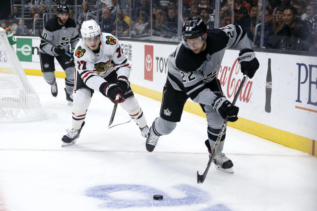 Los Angeles Kings forward Trevor Lewis (22) drives the puck away from Chicago Blackhawks forward Kirby Dach (77) during the second period of an NHL hockey game Saturday, Nov. 2, 2019, in Los Angeles. (AP Photo/Ringo H.W. Chiu)