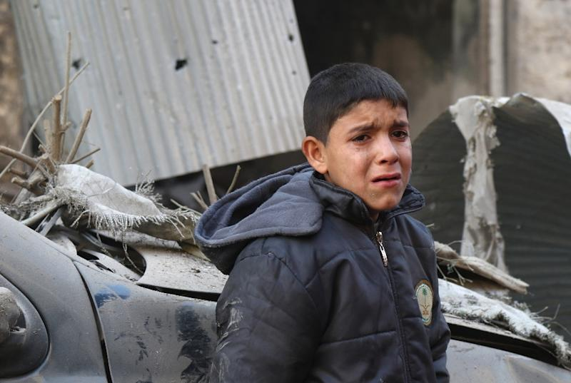 A Syrian boy cries as he stands next to a building hit by an air strike on the village of Maaret al-Numan, in the country's northern province of Idlib, on December 4, 2016 (AFP Photo/Mohamed al-Bakour)