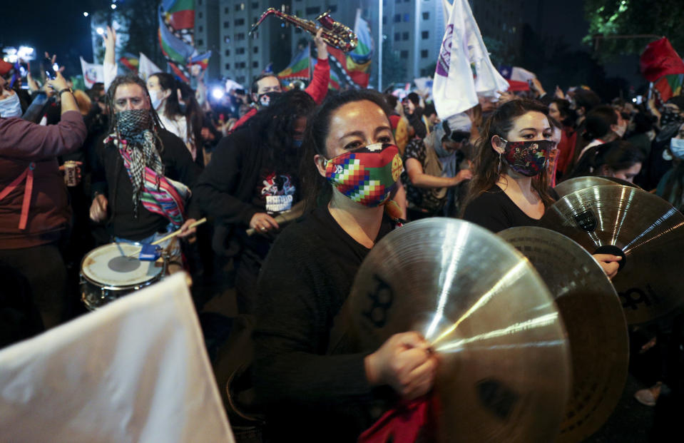 People play instruments at Plaza Italia on the day Chileans vote in a referendum to decide whether the country should replace its 40-year-old constitution, written during the dictatorship of Gen. Augusto Pinochet, in Santiago, Chile, Sunday, Oct. 25, 2020. (AP Photo/Esteban Felix)