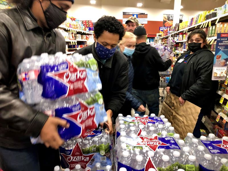 Shoppers crowd a display of bottled water at a United Supermarkets location not long after the city announced it had 2-3 hours of water left in Abilene