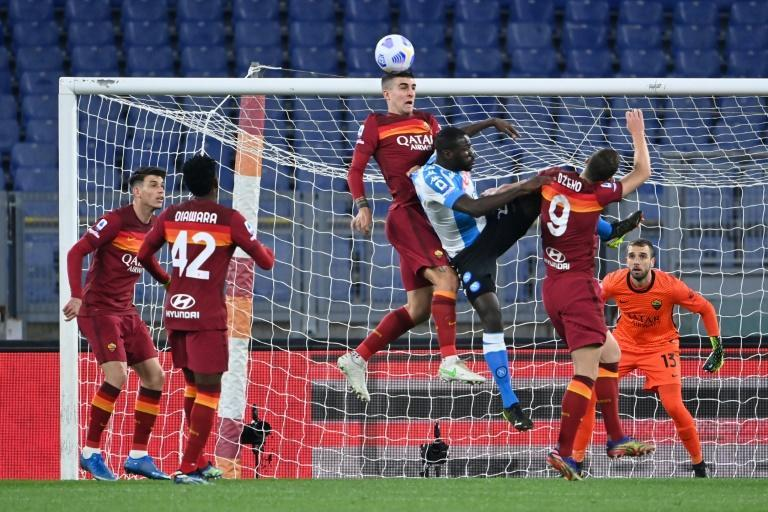Napoli defender Kalidou Koulibaly (C) is surrounded by Roma players in a Serie A aerial duel.