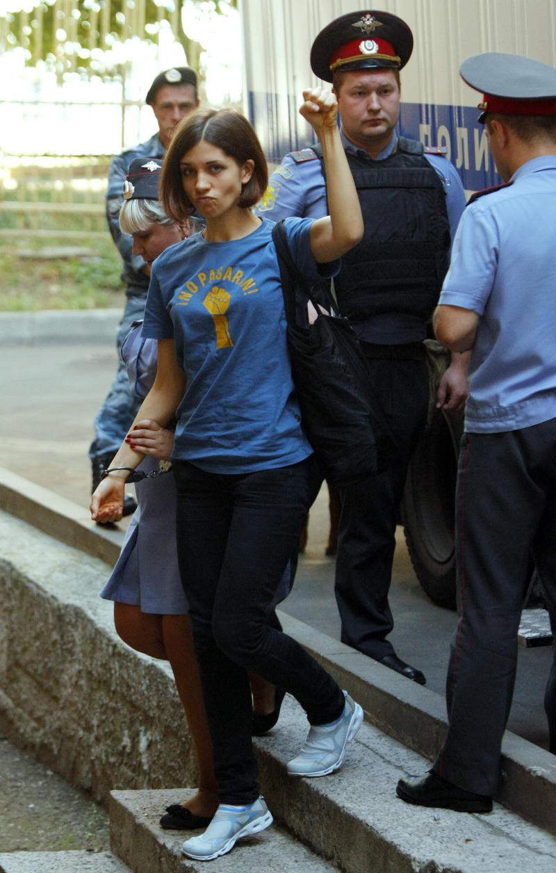 Nadezhda Tolokonnikova, left, a member of feminist punk group Pussy Riot is escorted to a court room in Moscow, Russia, Wednesday, Aug. 8, 2012. Prosecutors on Tuesday called for three-year prison sentences for feminist punk rockers who gave an impromptu performance in Moscow's main cathedral to call for an end to Vladimir Putin's rule, in a case that has caused international outrage and split Russian society.(AP Photo/Alexander Zemlianichenko)