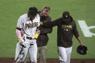 San Diego Padres manager Jayce Tingler, right, and a trainer help Fernando Tatis Jr, left, off the field after Tatis hurt his shoulder while swinging at a pitch in the third inning of a baseball game against the San Francisco Giants, Monday, April 5, 2021, in San Diego. (AP Photo/Derrick Tuskan)