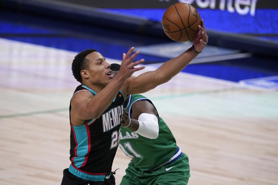 Memphis Grizzlies' Desmond Bane (22) loses control of the ball breaking to the basket as Dallas Mavericks' Tim Hardaway Jr., rear, defends in the first half of an NBA basketball game in Dallas, Monday, Feb. 22, 2021. (AP Photo/Tony Gutierrez)