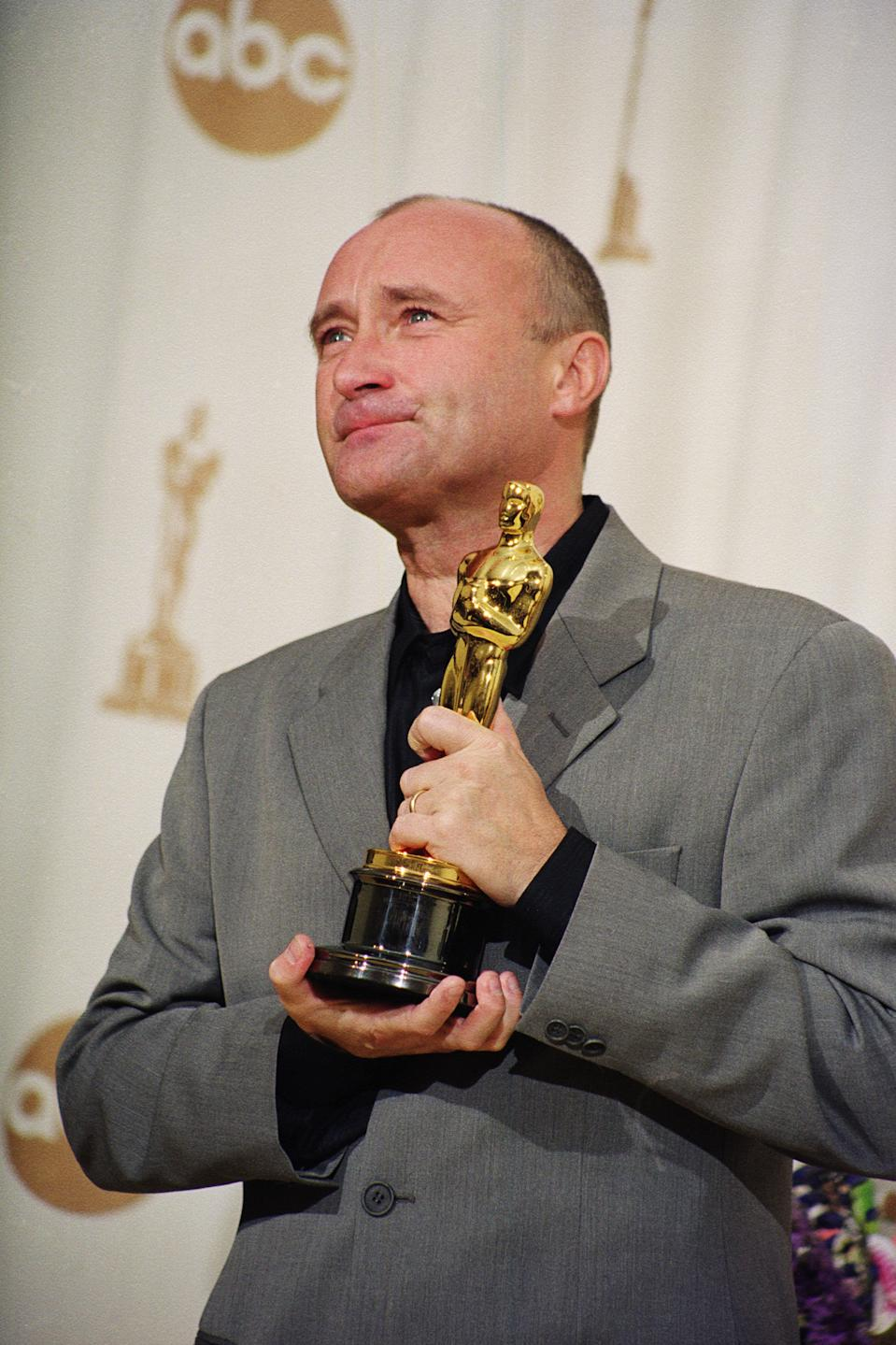 """Phil Collins poses with his 2000 Academy Award for Best Original Song, """"You'll Be in My Heart,"""" from the movie """"Tarzan."""" (Photo by Steve Starr/CORBIS/Corbis via Getty Images)"""