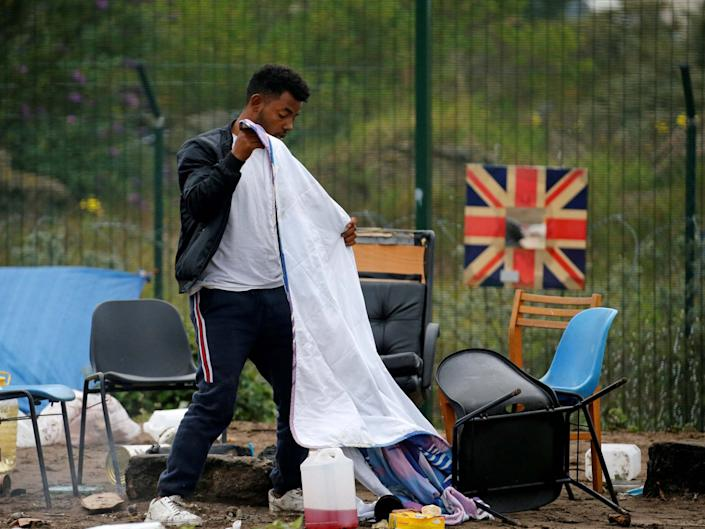 A man packs his belongings as police officers clear a refugee camp in Calais, France: REUTERS