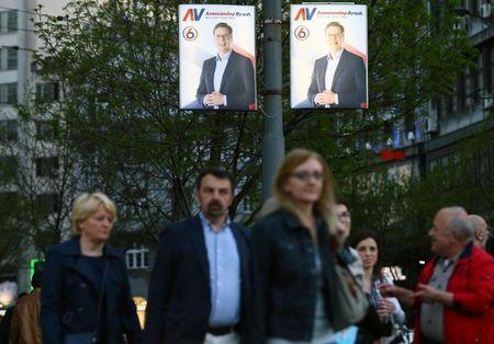 People walk past posters of Serbian Prime Minister and presidential candidate Aleksandar Vucic in Belgrade