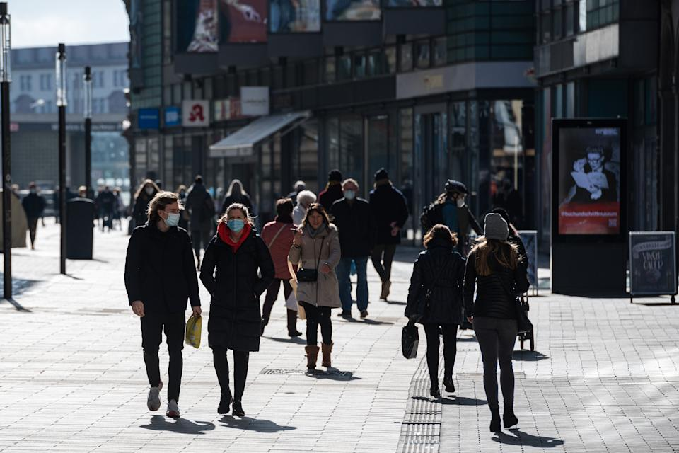 Passers-by walk in a shopping street as lockdown measures ease during the novel coronavirus pandemic on March 8, 2021 in Leipzig, Germany. Shops are opening nationwide today under strict conditions according to the infection rates in their respective regions. In areas with incidence rates between 50 and 100, which accounts for much of Germany, customers must book an appointment online to enter the store. Infection rates, which had been falling continuously since December, have levelled off and even begun to climb in recent weeks, which authorities attribute to the spread of the B117 coronavirus variant. (Photo by Jens Schlueter/Getty Images)