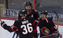 Ottawa Senators center Colin White and left-wing Nick Paul (center) congratulate right wing Evgenii Dadonov on his game-winning goal during the third period of an NHL game Monday, April 12, 2021, in Ottawa, Ontario. (Adrian Wyld/The Canadian Press via AP)