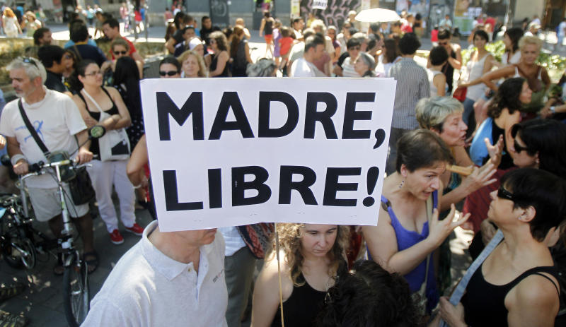 """A protester shows a banner that reads: """"Free Mother"""" during a protest against abortion law reform in Madrid, Spain, Sunday, July 29, 2012. (AP Photo/Andres Kudacki)"""