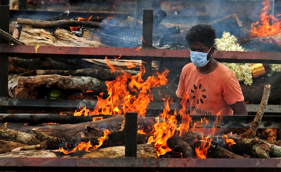 Funeral pyres for Covid-19 victims burn during a mass funeral at a makeshift cremation ground at Giddenahalli in the outskirts of Bangalore, India.