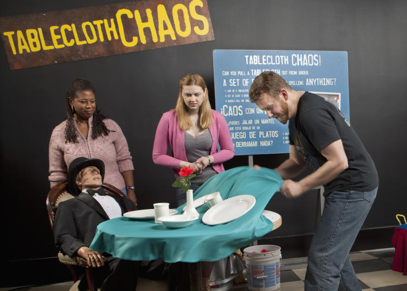 "In this March 5, 2012 photo provided by the Museum of Science and Industry, friends and family of museum staff are seen at the exhibit ""Tablecloth Chaos"" during setup for the show ""MythBusters: The Explosive Exhibition,"" modeled after the Discovery Channel television show ""Mythbusters"" at the Museum of Science and Industry in Chicago. The exhibit opens Thursday, March 15 and runs through Sept. 3. The planned national tour that will include stops at several other U.S. cities. (AP Photo/Museum of Science and Industry, J.B. Spector)"