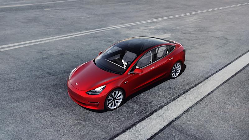 A red Tesla Model 3 on the highway.
