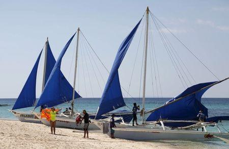 Tourists takes photographs along local sailboats on the island of Boracay, central Philippines January 18, 2016.    REUTERS/Charlie Saceda