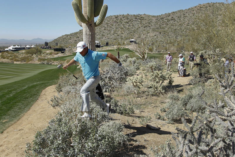 Northern Ireland's Graeme McDowell jumps over a bush after hitting out of the brush along the 17th fairway during a third round match against Shane Lowry of Ireland, at the Match Play Championship golf tournament, Saturday, Feb. 23, 2013, in Marana, Ariz. (AP Photo/Ross D. Franklin)
