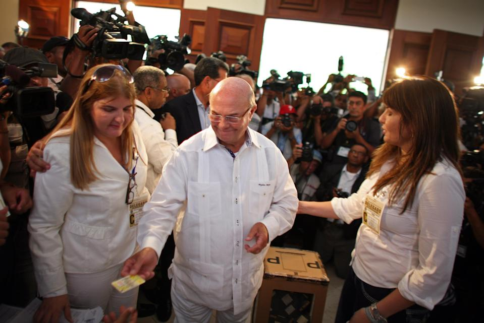 Former president and candidate of the opposition Dominican Revolutionary Party, Hipolito Mejia, center, hands over his ID card before casting his ballot during the presidential election in Santo Domingo, Dominican Republic, Sunday, May 20, 2012. (AP Photo/Ricardo Arduengo)
