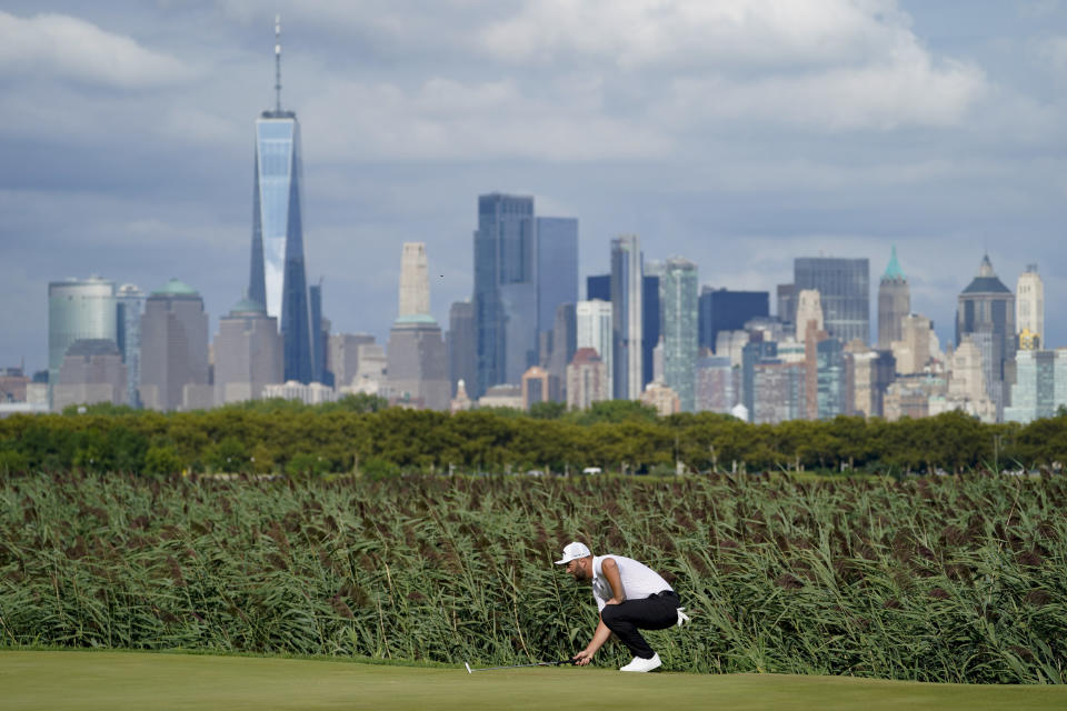 Jon Rahm, of Spain, reads the 14th green as the Manhattan skyline looms in the distance in the third round at the Northern Trust golf tournament, Saturday, Aug. 21, 2021, at Liberty National Golf Course in Jersey City, N.J. (AP Photo/John Minchillo)