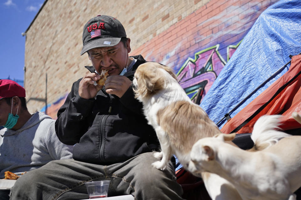 Dogs watch as Alfredo Martinez eats his lunch on the street, where he has been living for more than four months, in New York, Tuesday, April 13, 2021. Martinez, 38, a Mexican immigrant, used to work in construction but his hours were reduced when the pandemic started. Lack of steady income increased tensions with a roommate and he ended up in the street, where he has lived for the last four months. (AP Photo/Seth Wenig)