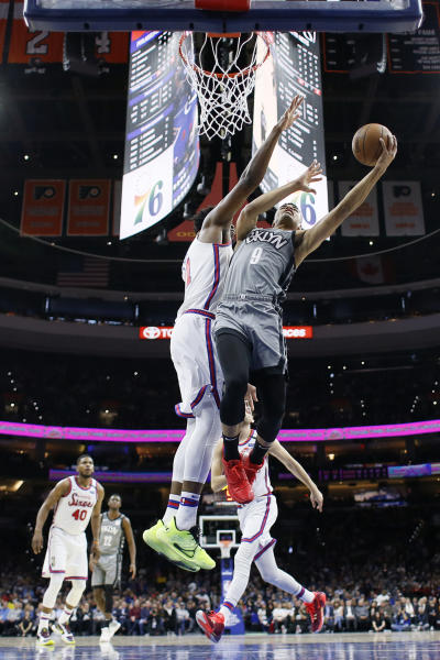 Brooklyn Nets' Timothe Luwawu-Cabarrot (9) goes up for a shot past Philadelphia 76ers' Joel Embiid (21) during the first half of an NBA basketball game, Thursday, Feb. 20, 2020, in Philadelphia. (AP Photo/Matt Slocum)
