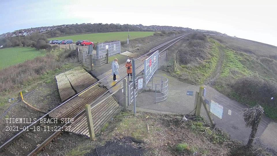 CCTV footage shows the women on the level crossing before they start taking photos. (SWNS)