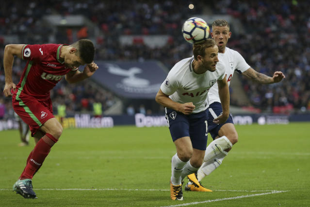 Tottenham's Harry Kane, centre, heads a corner towards goal as Tottenham's Toby Alderweireld, right, looks on and Swansea's Federico Fernandez competes for the ball during the English Premier League soccer match between Tottenham Hotspur and Swansea City at Wembley stadium in London, Saturday Sept. 16, 2017. (AP Photo/Tim Ireland)
