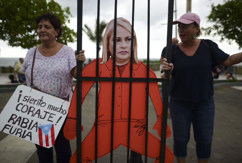 Protesters hold an image of Gov. Wanda Vázquez during a protest organized by Puerto Rican singer Rene Perez of Calle 13 over emergency aid that until recently sat unused in a warehouse amid ongoing earthquakes, in San Juan, Puerto Rico, Thursday, Jan. 23, 2020. Protesters are demanding Vázquez's ouster. (AP Photo/Carlos Giusti)