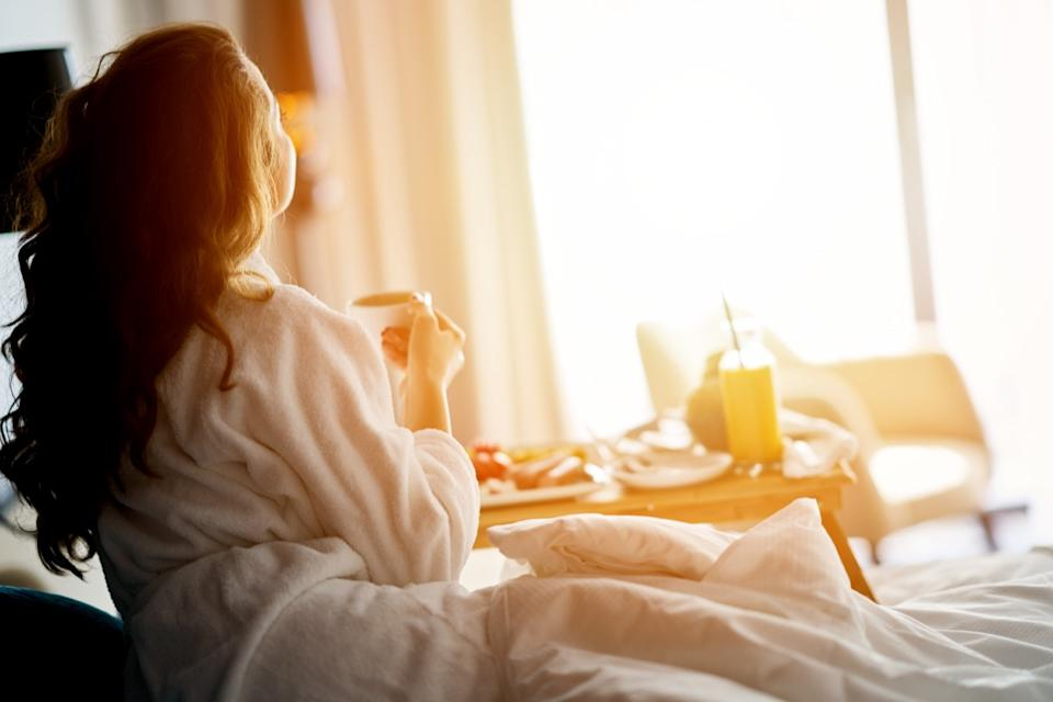 a bougie woman eating breakfast in bed
