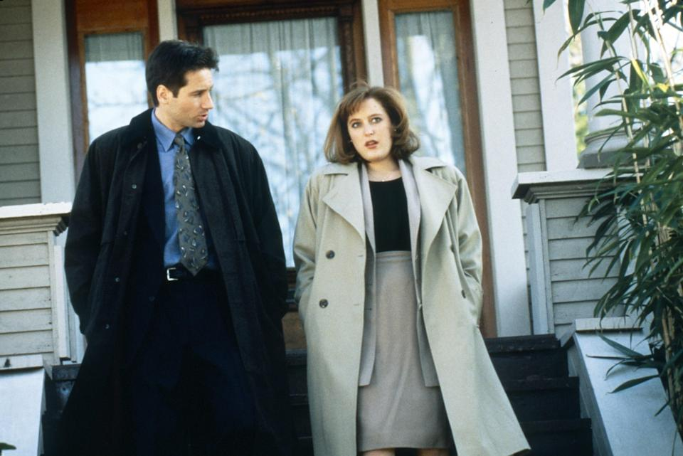 David Duchovny and Gillian Anderson walk down the stairs outside a house