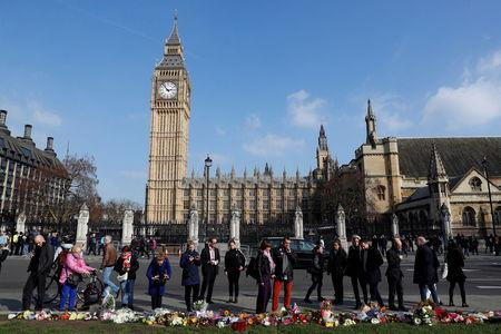 People look at tributes left in Parliament Square following a recent attack in Westminster, London, Britain March 24, 2017. REUTERS/Darren Staples