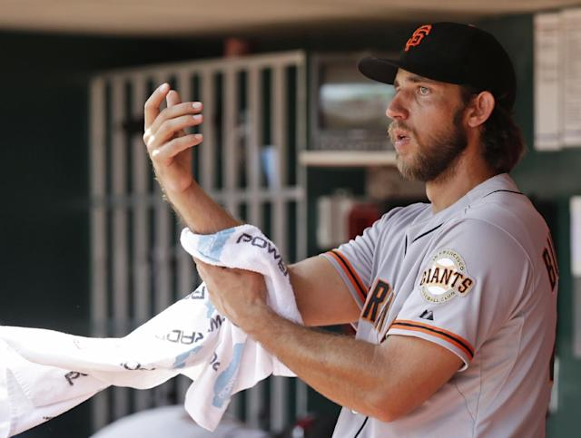San Francisco Giants starting pitcher Madison Bumgarner wipes his arms after he was taken out at in the eighth inning of a baseball game against the Cincinnati Reds, Thursday, June 5, 2014, in Cincinnati. Bumgarner earned his eighth win giving up one run on three hits in eight innings. (AP Photo/Al Behrman)