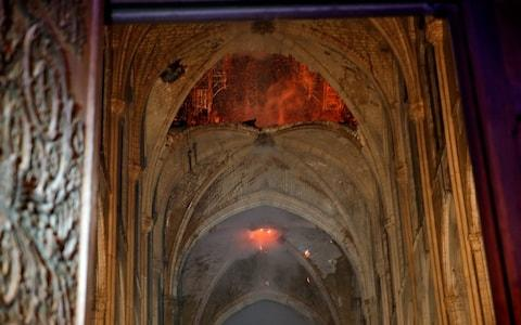 Flames and smoke are seen as the interior continues to burn inside the Notre Dame Cathedral - Credit: Reuters
