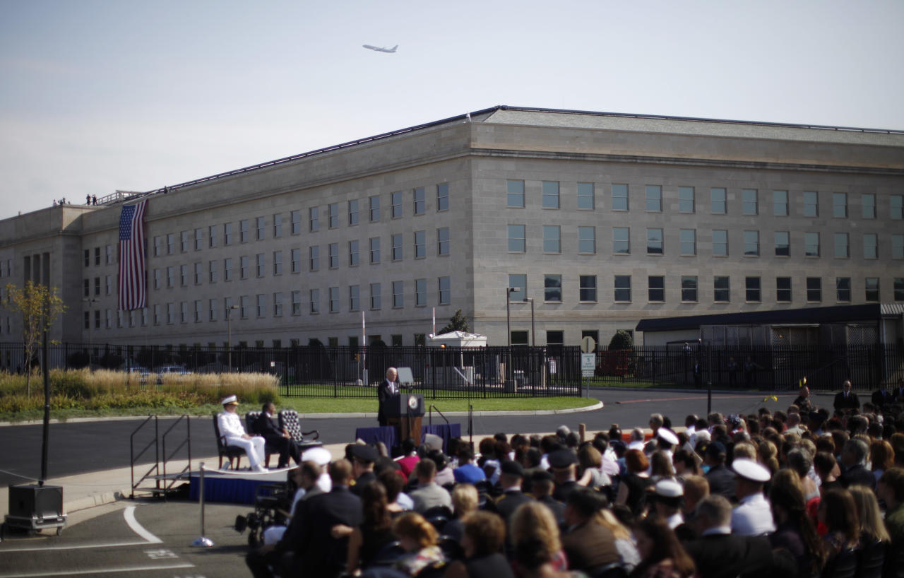 A commercial airliner flies over the Pentagon as a United States flag hangs over the side of the building where on September 11, 2001 a passenger jet was flown into the building, as Vice President Joe Biden delivers remarks during ceremonies marking the 10th anniversary of the 9/11 attack on the Pentagon, in Washington September 11, 2011.  (REUTERS/Jason Reed)