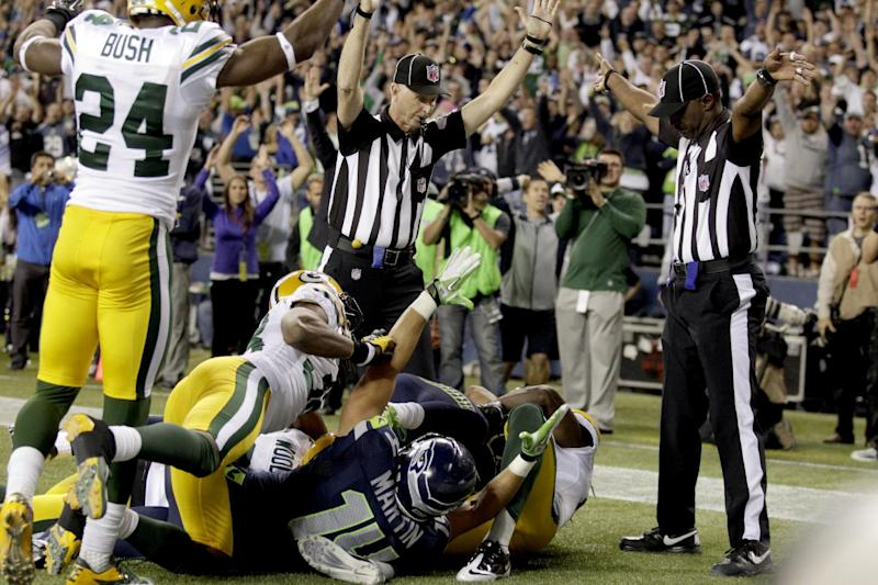 FILE - In this Sept. 24, 2012, file photo, an official, rear center, signals for a touchdown by Seattle Seahawks wide receiver Golden Tate, obscured, as another official, at right, signals a touchback on the controversial last play of an NFL football game against the Green Bay Packers in Seattle. The Seahawks won 14-12. The NFL and the referees' union have reached a tentative contract agreement on Wednesday, Sept. 26, ending an impasse that began in June when the league locked out the officials and used replacements instead. (AP Photo/Stephen Brashear, File)