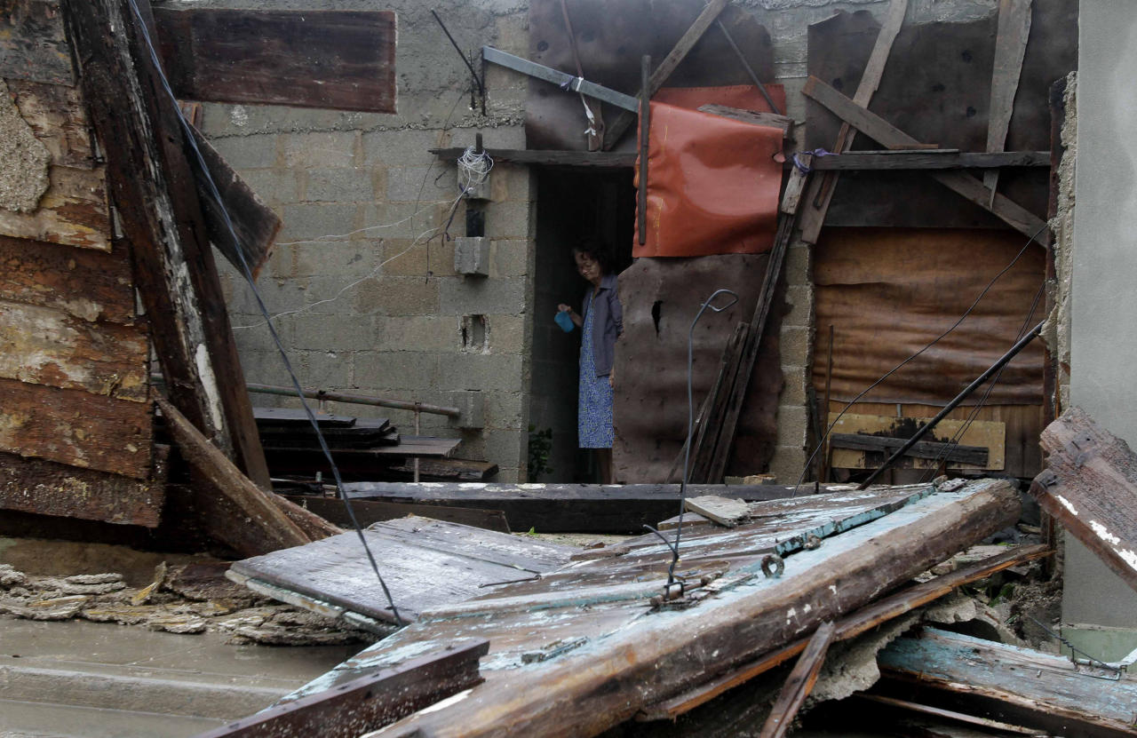 A woman peers from the doorway of her cement home that is being built within the frame of an wooden home, which was partially knocked down by the passing of Huriccane Sandy in Gibara, Cuba, Thursday, Oct. 25, 2012. Hurricane Sandy blasted across eastern Cuba on Thursday as a potent Category 2 storm and headed for the Bahamas after causing at least two deaths in the Caribbean. (AP Photo/Franklin Reyes)