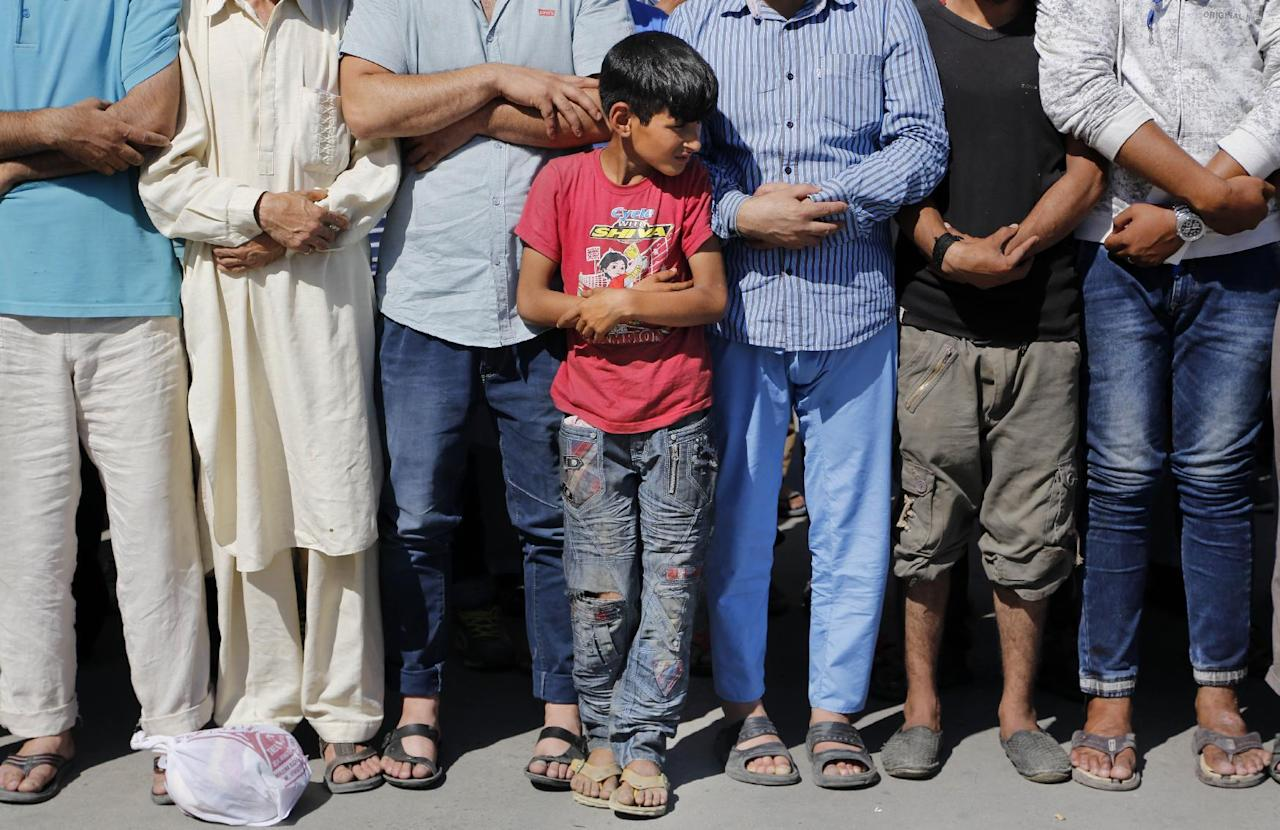 A young Kashmiri boy joins adults in offering funeral prayers for a Kashmiri civilian Ghulam Mohammad Mir, who succumbed to injury allegedly attained during a protest last week, outside a hospital in Srinagar, India, Wednesday, July 20, 2016. The largest street protests in recent years in the disputed region, that left dozens of people dead and hundreds injured erupted more than a week ago after Indian troops killed a popular young rebel leader. (AP Photo/Mukhtar Khan)