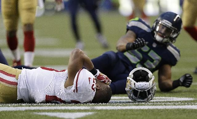 San Francisco 49ers' LaMichael James lays on the field after being hit on a punt return during the first half of the NFL football NFC Championship game against the Seattle Seahawks, Sunday, Jan. 19, 2014, in Seattle. (AP Photo/Marcio Jose Sanchez)