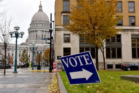 A sign directs voters towards a polling place near the state capitol in Madison, Wisconsin, U.S. November 6, 2018. REUTERS/Nick Oxford