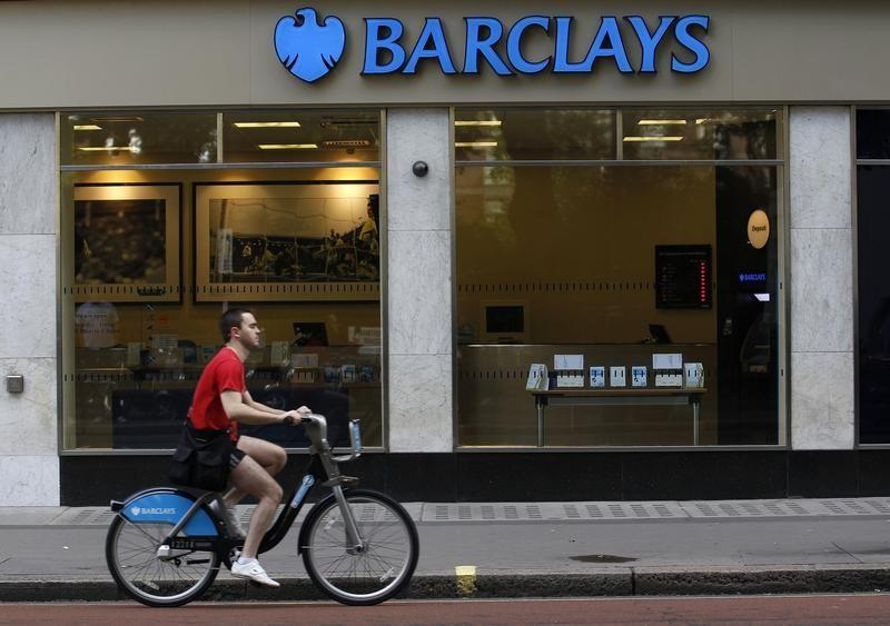 A man rides a bicycle past a Barclays bank in London