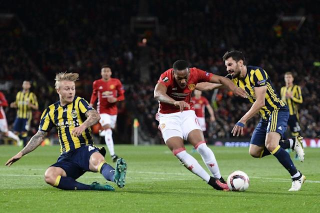 Fenerbahce's Turkish defender Sener Ozbayrakli (R) fouls Manchester United's French striker Anthony Martial (C) on October 20, 2016 (AFP Photo/Oli Scarff)