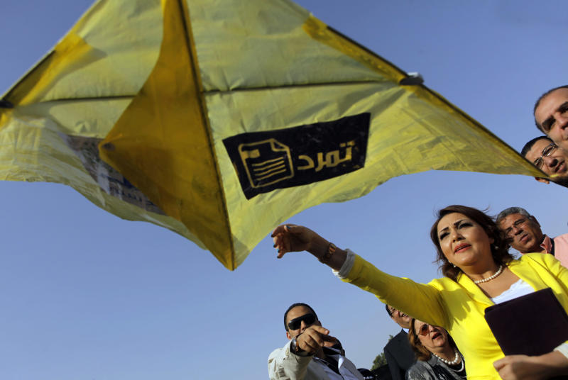 """Gameela Ismail, a leading member of the Egyptian Constitution party, flies a kite with the logo of Tamarod, Arabic for """"rebel"""", a campaign calling for the ouster of Egyptian President Mohammed Morsi and for early presidential elections, in Cairo, Egypt, Friday, June 7, 2013. Morsi's Muslim Brotherhood has dismissed the campaign as irrelevant, even illegal, but the signature drive has stirred up Egypt's politics as the president nears the end of his tumultuous first year in office. (AP Photo/Amr Nabil)"""