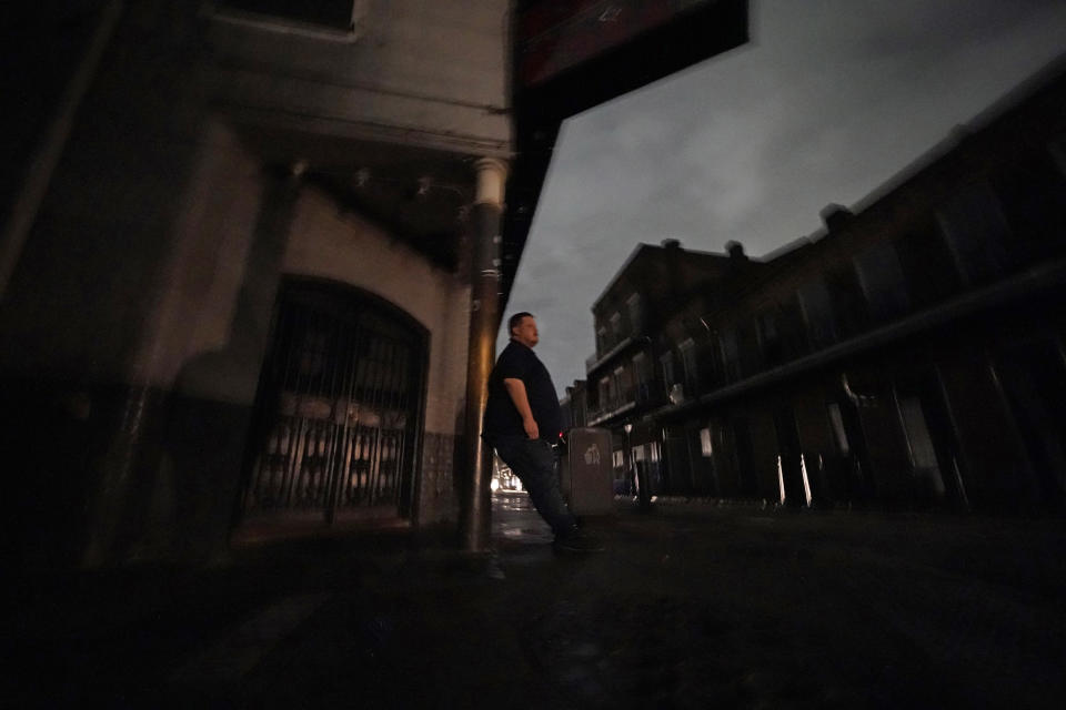 Greg Nazarko, manager of the Bourbon Bandstand bar on Bourbon Street, leans against a pole outside the club where he rode out Hurricane Ida that knocked out power in New Orleans, Monday, Aug. 30, 2021. (AP Photo/Gerald Herbert)