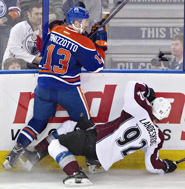 Colorado Avalanche's Gabriel Landeskog (92) is checked by Edmonton Oilers' Steven Pinizzotto (13) during second period NHL hockey action in Edmonton, Alberta, on Tuesday April 8, 2014. (AP Photo/The Canadian Press, Jason Franson)