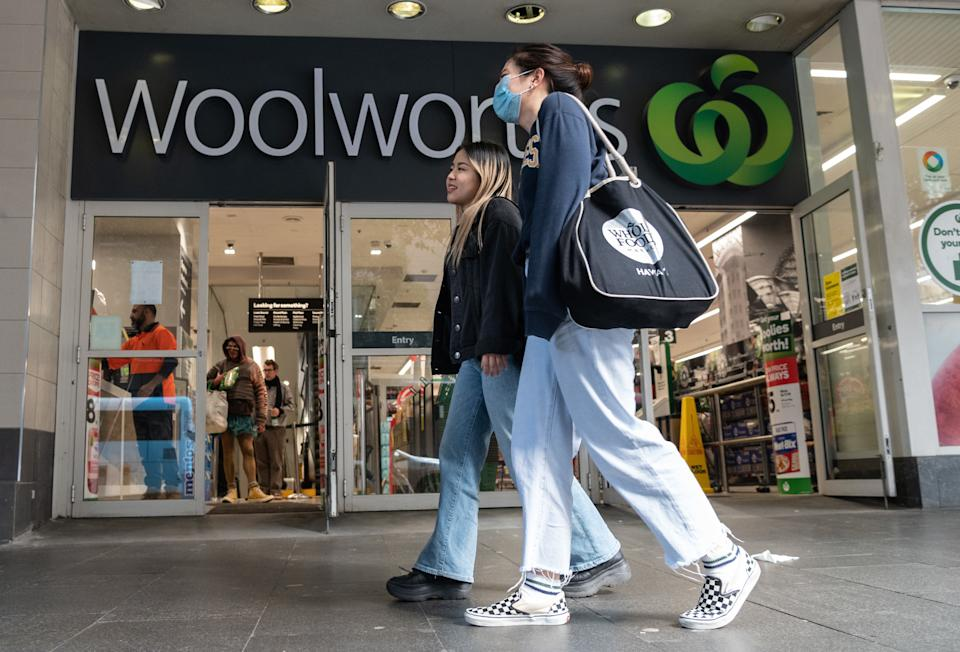 A person wearing a face mask in front of a Woolworths shop in Sydney.