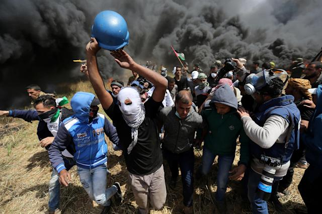 <p>Palestinians evacuate a wounded journalist during clashes with Israeli troops at the Israel-Gaza border at a protest demanding the right to return to their homeland, in the southern Gaza Strip, April 6, 2018. (Photo: Ibraheem Abu Mustafa/Reuters) </p>