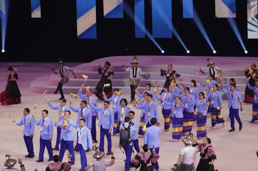 Myanmar's athletes hold flags during the opening ceremony of the 30th South East Asian Games at the Philippine Arena, Bulacan province, northern Philippines on Saturday, Nov. 30, 2019. (AP Photo/Aaron Favila)